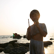 """A young boy fishes at sundown along the rocky shores of Phu Quoc Island, Vietnam. Phu Quoc is Vietnam's newest beach destination, just a 50 minute flight away from Ho Chi Minh City. With its proximity closer to the Cambodian mainland than to Vietnam, it was a launching pad for thousands of """"Boat People"""" refugees during the 1970s and 1980s, and has a strong military presence. However, with tourism in Vietnam booming, the government has opened up this largely agricultural and fishing island to foreign tourists, who can now enjoy sunsets on the only beaches in Vietnam that face west."""