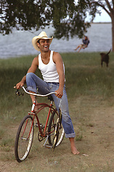 cowboy enjoying time on a retro bicycle with fish in his hand, dog and woman in the background by a lake