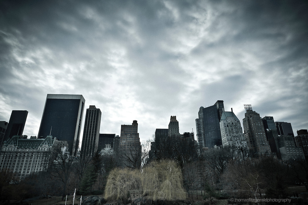 A moody dark cloudy sky looms over the buildings and trees of Central Park, NYC