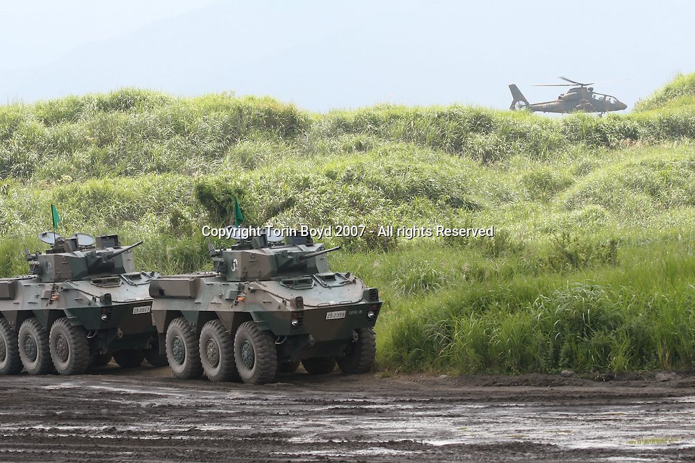 "These are 87RCV (Reconnaissance Combat Vehicle) named the 87REV Blackeye in Japan (in the background is an OH-X scout helicopter nicknamed ""Ninja""). They were demonstrated during the Japan Ground Self Defense Force's annual live fire exercise at the Higashi Fuji training range in Gotemba, Shizuoka Prefecture. Officially entitled ""Fire Power 2007 in Fuji"", this sold-out public event held on August 26, 2007 at the base of a cloud obscured Mt. Fuji involved about 2000 military personnel, 60 tanks and armored vehicles and 20 aircraft. Japan spends nearly $40 billion annually on it's defense budget and its growing strength is the topic of much debate. This is due to Japan's political power brokers who want to rearm Japan by revising Article 9 of the constitution, thus changing the pacifist policy of the country. This is of much concern to Japan's Asian neighbors, but is also encouraged by the United States government."