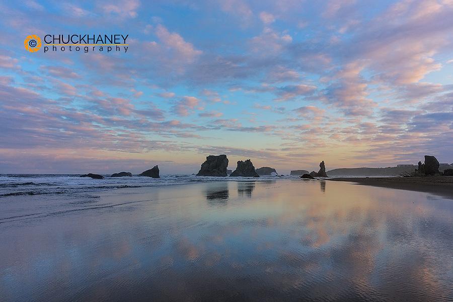 Clouds reflect in wet sand at sunrise at Bandon Beach in Bandon, Oregon, USA