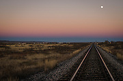 Train tracks fade into the horizon at dusk along The Mother Road: Historic Route 66 near Santa Rosa, New Mexico.