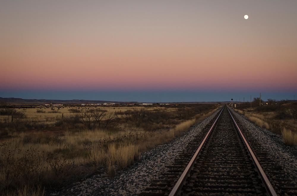 Train tracks fade into the horizon at dusk along The Mother Road: Historic Route 66 near Santa Rosa, New Mexico.