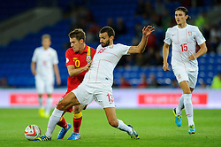 Aaron Ramsey of Wales (Arsenal) is challenged by Ivan Radovanovic of Serbia (Chievo) during the first half of the match - Photo mandatory by-line: Rogan Thomson/JMP - Tel: Mobile: 07966 386802 10/09/2013 - SPORT - FOOTBALL - Cardiff City Stadium - Cardiff -  Wales V Serbia- World Cup Qualifier.