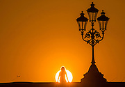 UNITED KINGDOM, London: 20 April 2016 A commuter watches the sunset on Putney Bridge this evening after another sunny day in the capital. Rick Findler / Story Picture Agency