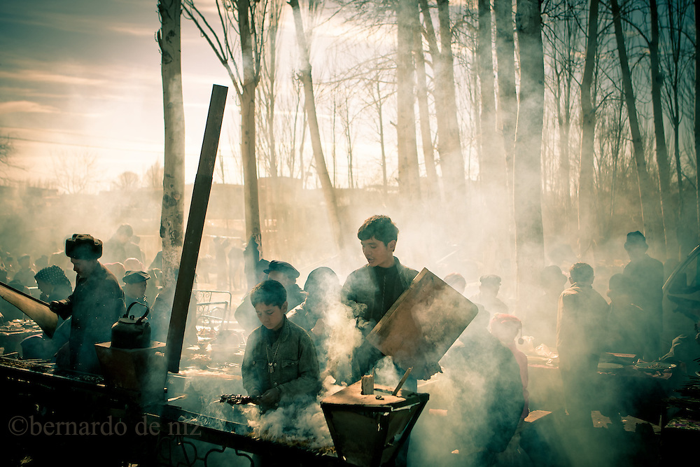 Uyghur boy cook kebabs, in the street market in Kashgar, ,China, on February. 21, 2010. Photographer: Bernardo De Niz