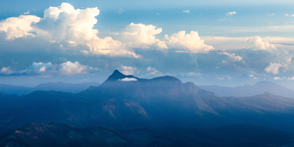 The last rays of the setting sun illuminate the clouds above and surrounding Mt Warning. Seen from the Best Of All Lookout in Springbrook National Park.
