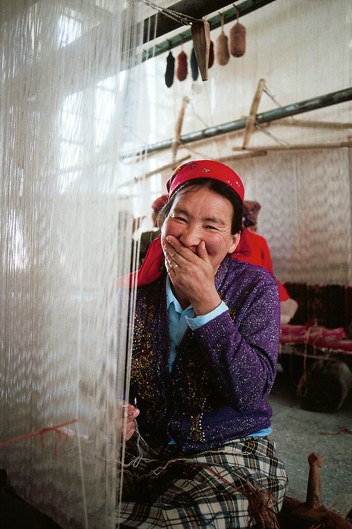 Rug weaver in a shop in Khotan, Xinjiang Province, China.