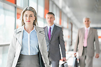 Beautiful young businesswoman walking with male colleagues in background at train platform