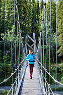 A female hiker crosses the Riley Creek suspension bridge on the Triple Lakes Trail in Denali National Park, Alaska.
