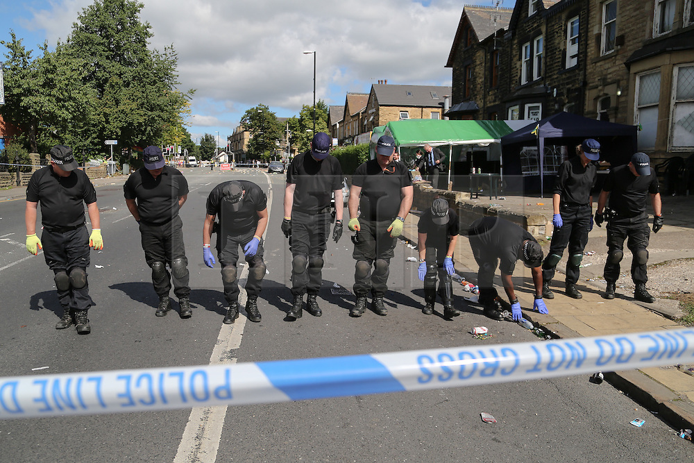 © Licensed to London News Pictures. 29/08/2016. Leeds, UK. Police search in a line at what is believed to be the scene of shooting that took place last night. This is as yet unconfirmed by the police. The incident happened in the Chappeltown area of Leeds where the West Indian Carnival is taking place this weekend. Photo credit : Ian Hinchliffe/LNP