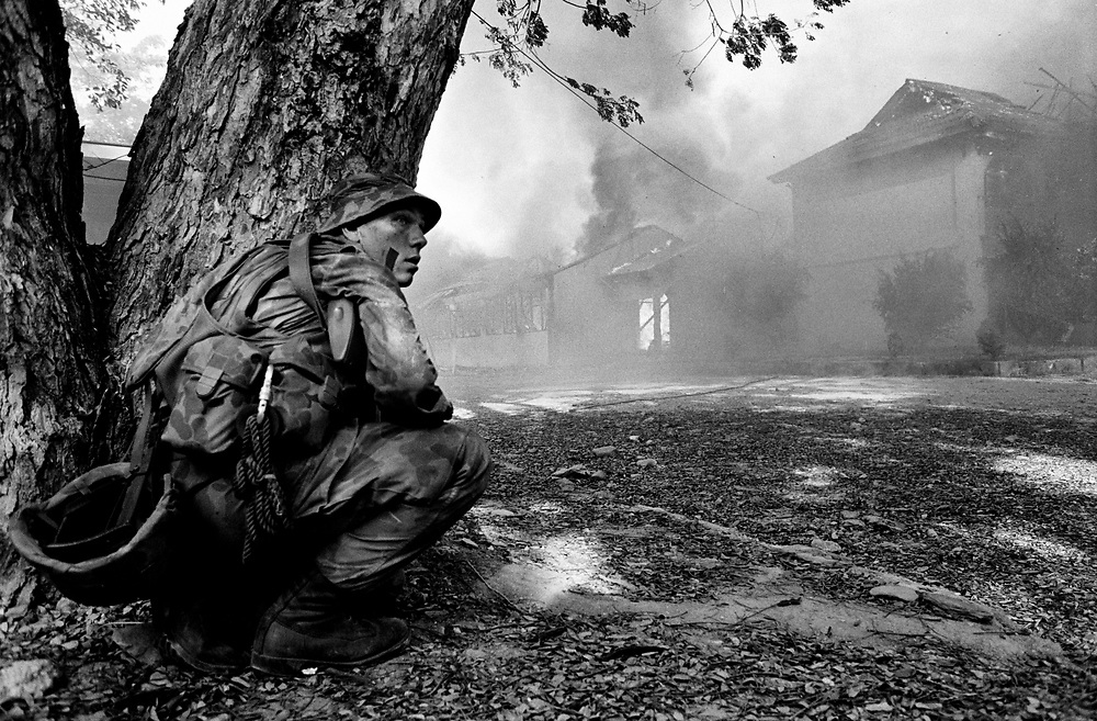 An Australian soldier takes cover as Dili burns. East Timor September 1999