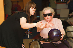Staff with visually-impaired wheelchair user at ten pin bowling alley.