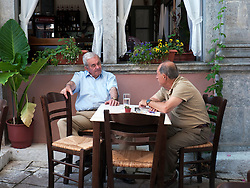 Two Greek men having conversation in a cafe in Agiassos on Lesvos Island in Greece