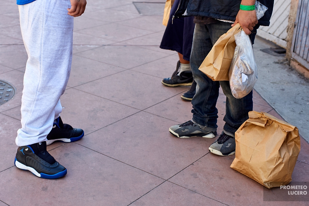 With no shoelaces in their shoes and with a paper bag, a group of deported young people is spotted when they get out of El Chaparral Sentry .  // Un grupo de jóvenes recién deportados con una bolsa de papel y sin agujetas en los zapatos sale de la Garita El Chaparral (Prometeo Lucero)