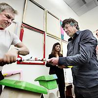 Nederland, Amsterdam , 1 april 2011..24-uurs iPad-performance van Kamagurka .Het hoofdevenement van Move It! is een 24 uur durende performance van Kamagurka, die daarmee fysiek uiting geeft aan het thema van de avond. Donderdag 31 maart begint hij om 12 uur op een iPad te werken, in een naast het auditorium gelegen ruimte die dienst doet als atelier. De werken worden direct afgedrukt, opgespannen en opgehangen in dezelfde zaal, zodat het publiek getuige kan zijn van een gestaag groeiende tentoonstelling. Vrijdag 1 april vlak voor 12 uur zal Kamagurka de gemaakte prints publiekelijk vernietigen met een grote tuinshredder. De volgende dag publiceert NRC een groot deel van de werken in een speciale bijlage, als vergankelijk overblijfsel van de performance. De snippers worden vervolgens verbrand in de tuin van het Nationaal Glasmuseum in Leerdam en verdeeld over acht door Kamagurka ontworpen urnen die vanaf 16 april onderdeel zijn van het kunstproject Het Transparante Lichaam. Zo krijgt het werk steeds in andere vorm een nieuw leven. .Multitalent Kamagurka (artiestennaam van Luc Zeebroek, geboren 1956) is bekend van zijn cartoons voor vele (inter)nationale media, waaronder NRC, Vrij Nederland, HP/De Tijd en HUMO, zijn radio- en tv-programma's, toneelstukken en stripboeken..Op de foto rechts in zwarte shirt Luc Zeebroek alias Kamagurka..Foto:Jean-Pierre Jans