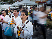 "04 MARCH 2015 - BANGKOK, THAILAND: People pray while others in a procession around the ""wiharn,"" or prayer hall, pass them at Wat Benchamabophit on Makha Bucha Day. Makha Bucha Day is an important Buddhist holy day and public holiday in Thailand, Cambodia, Laos, and Myanmar. Many people go to temples to perform merit-making activities on Makha Bucha Day. Wat Benchamabophit is one of the most popular Buddhist temples in Bangkok.    PHOTO BY JACK KURTZ"
