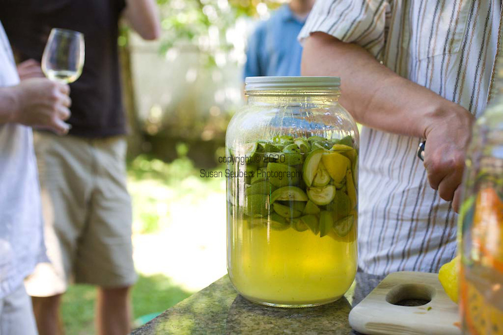 A group of friends gather in the back yard to have a nocino making party. Nocino is a sticky dark brown liqueur from the Emilia-Romagna region in Northern Italy. Nocino is made from unripe green walnuts steeped in spirit. It has an aromatic but bittersweet flavor.