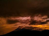 Lightning strikes near Fuego and Acatenango volcanoes near Antigua, Guatemala at sunset.