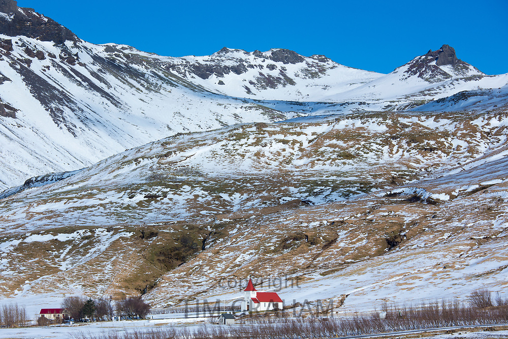 Church with red roof and hamlet village at Huammur by Eyjafjallajokul icecap in Thorsmork Valley, Katla Geopark, South Iceland