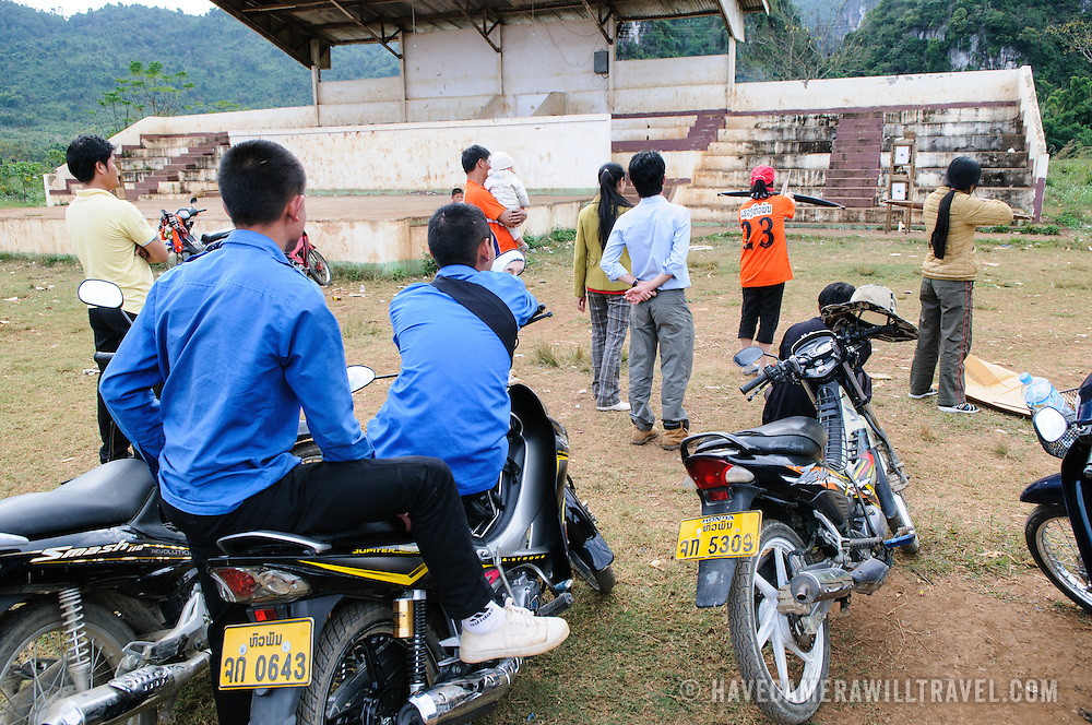 Student spectators line up on their scooters and bikes to watch a crossbow contest on a dirt playing field among the rugged terrain near Vieng Xai in northeast Laos.