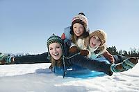 Three teenage girls lying on a sledge
