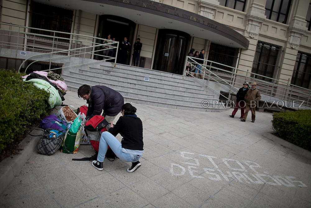 Amalia Torres 51, (L) and a friend pack up their belongings one day before her eviction takes place outside the Madrid's Council Housing Office where she spent the night claiming to stop her eviction on April 3, 2013 in Madrid, Spain. Graffiti reads 'Stop Evictions'. The Mortgage Holders Platform (PAH) and other anti evictions organizations are organizing 'escraches' since several weeks ago outside Popular Party deputies houses and offices to demand the vote for a Popular Legistative Initiative (ILP) to stop evictions, regulate dation in payment and social rent.