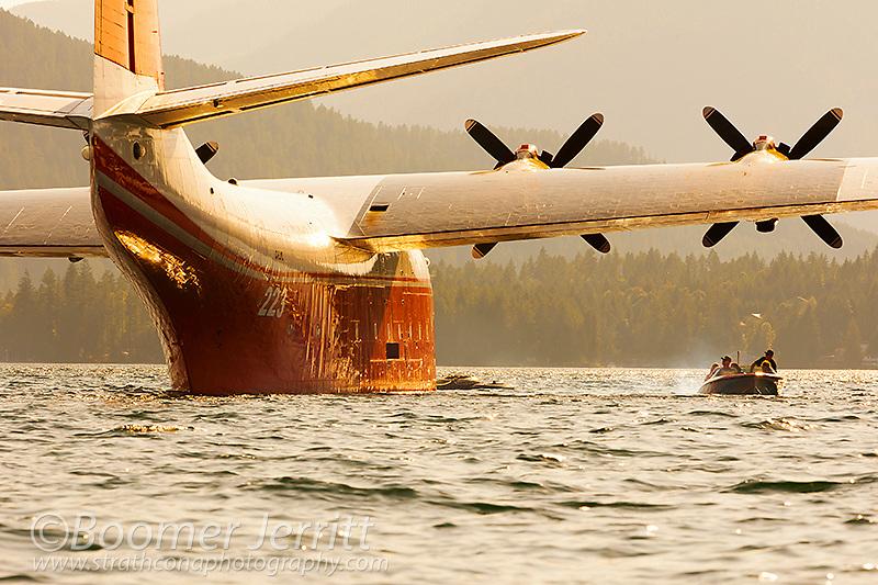 The huge Martin Mars Water Bomber, Mars Hawaii set against a setting sun at it's home base on Sproat Lake in Port Alberni.  Port Alberni, Vancouver Island, British Columbia, Canada