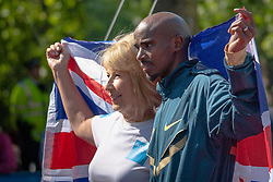 London, May 25th 2014. BBC Royal Correspondent Jenny Bond and Olympic long distance medalist Mo Farrah pose at the start of the BUP 10km run in London.