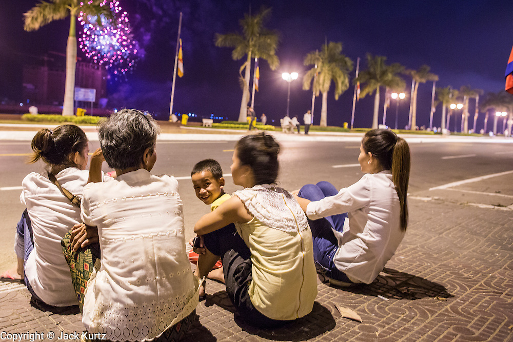 """04 FEBRUARY 2013 - PHNOM PENH, CAMBODIA: Cambodians on Sisowath Quay watch a fireworks show over the riverfront during the cremation of their former King Norodom Sihanouk during the King-Father's cremation service in Phnom Penh. Norodom Sihanouk (31 October 1922- 15 October 2012) was the King of Cambodia from 1941 to 1955 and again from 1993 to 2004. He was the effective ruler of Cambodia from 1953 to 1970. After his second abdication in 2004, he was given the honorific of """"The King-Father of Cambodia."""" Sihanouk died in Beijing, China, where he was receiving medical care, on Oct. 15, 2012.    PHOTO BY JACK KURTZ"""