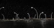 People walking on a rainy night on the Tel Aviv boardwalk by the sea