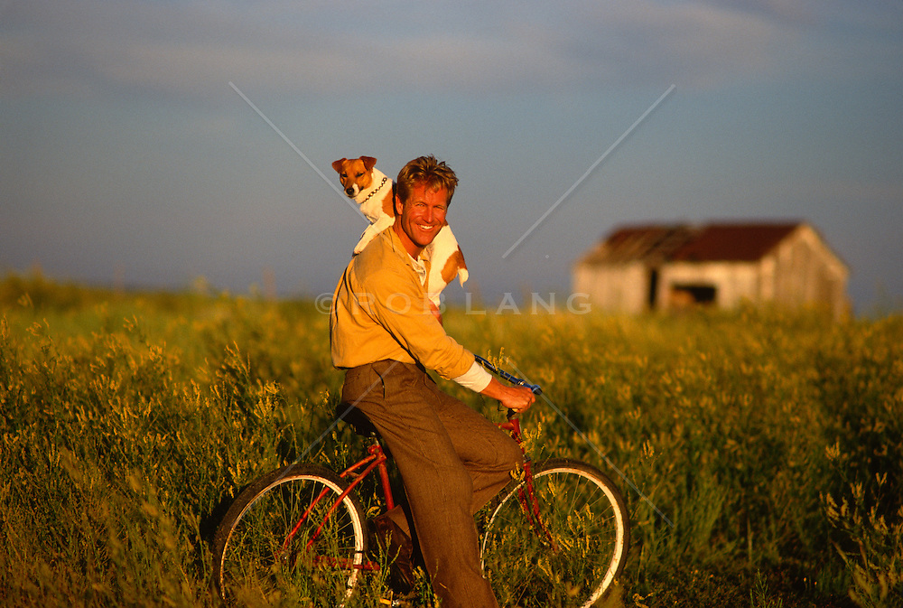 Man sitting on his bike  with his jack russell on one shoulder out in a field in New Mexico
