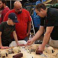 Robbie Martin of Adeptus Tupelo shows Carson Robinson, 12, and his father Charlie how to play Star Wars Legion Saturday at the Tupelo Comic Con