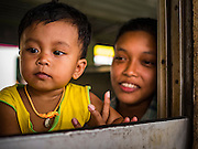 "03 JANUARY 2017 - BANGKOK, THAILAND:          A woman and her daughter on the Bangkok-Yala train Tuesday. Travelers flocked to Bangkok bus and train stations Tuesday, the last day of the long New Year's weekend in Thailand. The New Year holiday in Thailand is called the ""seven deadly days"" because of the number of fatal highway and traffic accidents. As of Monday Jan 2, 367 people died in highway accidents over the New Year holiday in Thailand, a 25.7% increase over the same period in 2016.         PHOTO BY JACK KURTZ"