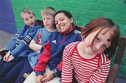 Multiracial group of children sitting on bench in school playground,