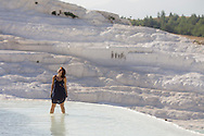 A tourist wet her feet at one of the pools at Pamukkale. The hard, white mineral deposits, which from a distance resemble snow, are caused by the high mineral content of the natural spring water which runs down the cliff and congregates in warm pools on the terraces. This is such a popular tourist attraction that strict rules had to be established in order to preserve its beauty, which include the fact that visitors may no longer walk on the terraces. Those who want to enjoy the thermal waters, however, can take a dip in the nearby pool, littered with fragments of marble pillars.