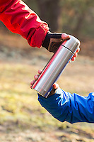 Cropped image of hikers holding insulated coffee container in forest