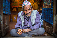 An old Thangka painter from Bhaktapur, Nepal, is smocking a cigarette on the entry of his shop. The hat on his head is called &quot;Dhaka Topi&quot; and is usually given away as gifts during Dashain and Tihar festivals. <br /> Photo by Lorenz Berna