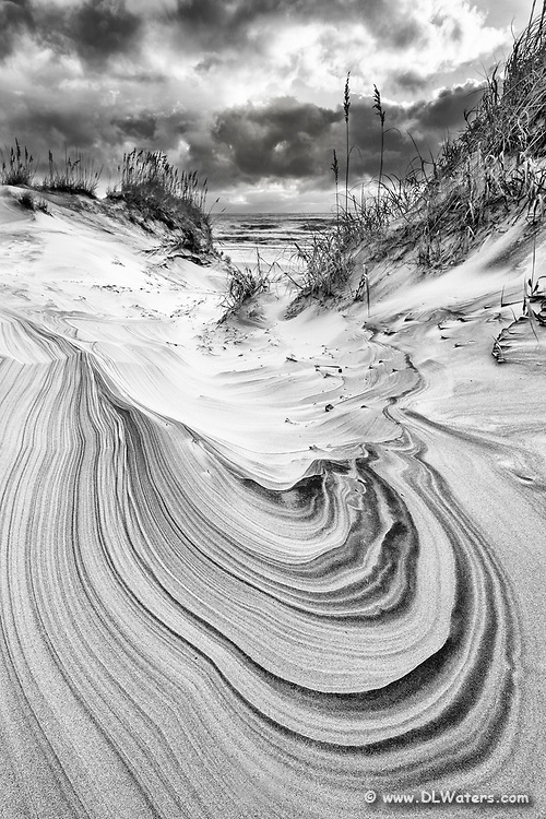 Black and white sand dune and sky in Corolla on the Outer Banks of North Carolina.