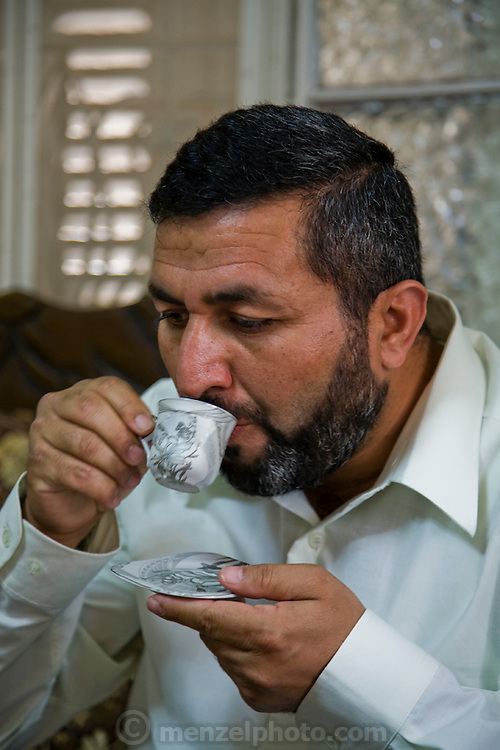 Palestinian guide and driver Abdul-Baset Razem drinks coffee in his living room in a Palestinean village in East Jerusalem. (Abdul-Baset Razem is featured in the book What I Eat: Around the World in 80 Diets.) MODEL RELEASED.