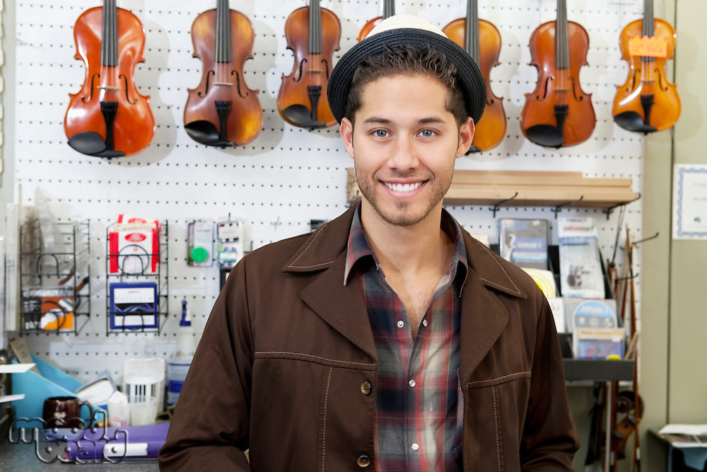 Portrait of a happy young music store owner