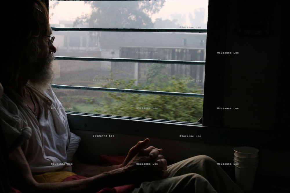 An elderly traveller wakes up to a foggy morning while riding in an Indian train through Bharatpur, Rajasthan, India..Photo by Suzanne Lee
