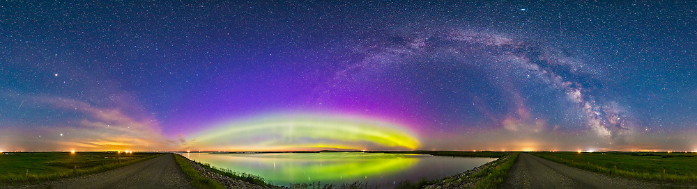The arc of the Northern Lights and auroral oval over Crawling Lake, Alberta, as well as the arch of the summer Milky Way, in a 360&deg; panorama, on the night of June 24/25, 2017. The location was on the causeway on the dam at the south end of the reservoir/lake. <br /> <br /> The sky is blue from the glow of all-night perpertual twilight at this time of year near solstice. <br /> <br /> Arcturus and the Big Dipper are at left, with Jupiter just setting amid the clouds at far left. Polaris is just left of the peak of the auroral arc which is centred slightly east of north from my longitude. The Summer Triangle stars are at right over the roadway. The galactic centre is above the south horizon at far right. Saturn is amid the Dark Horse in the Milky Way at far right, low above the horizon. <br /> <br /> This is a stitch of 8 segments with the 14mm Rokinon SP lens, mounted vertically, each 30 seconds at f/2.5 and ISO 3200 with the Canon 6D. Panning and shooting was done automatically with the SYRP Mini Genie in its panorama mode. Stitched with PTGui.