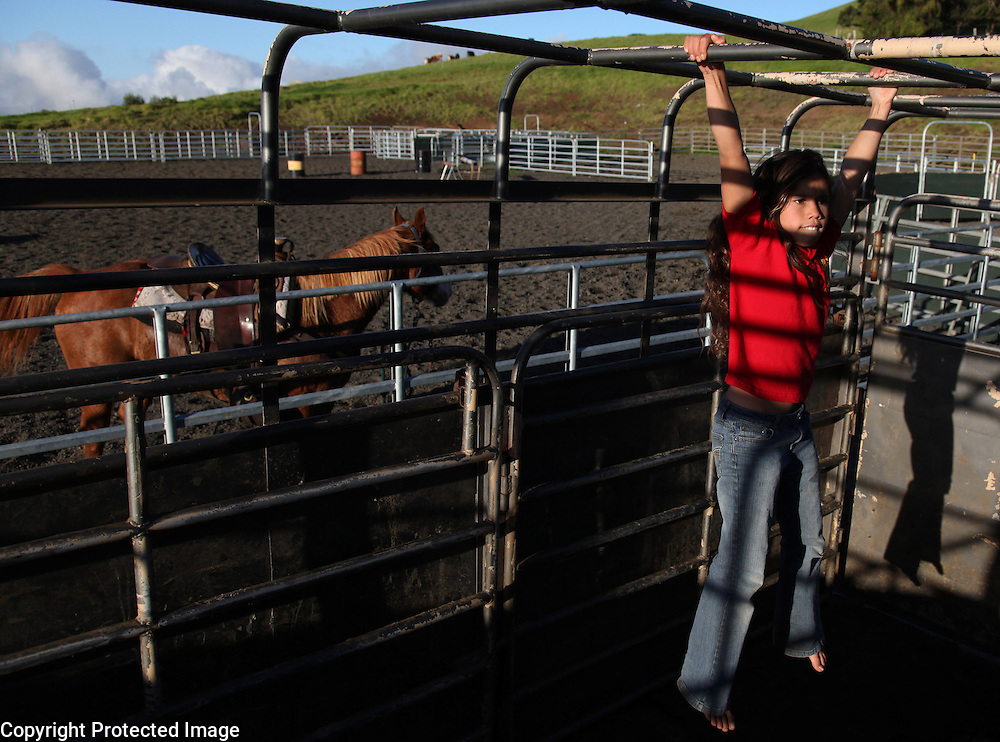 "Nahe Tachera, 9, whose great-grandfather, grandfather and father are or were all cowboys, uses the horse trailer as her jungle-gym on Kahua Ranch in North Kohala, Hawaii.  Nahe and her sister, Kamehana, 11, live with their father, Wayne Tachera, in ""cowboy housing"" on the ranch.  The girls learned to ride horses as toddlers and have grown up with the ranch as their playground.  ""My dad's work is great.  While he works, we can play around the ranch and he doesn't have to worry about us"", says Nahe.  ""We're definitely cowgirls"", adds Kamehana who regularly competes in rodeos and who can often be found cutting photos of cowboys out of magazines and pasting them in her scrapbook."