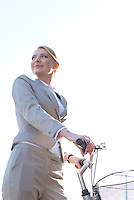 Low angle view of businesswoman holding bicycle against clear sky