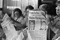 "08 Aug 1974, Washington, DC, USA --- Women at Washington National Airport read the  newspaper with ""Nixon Resigning"" as the headline on its front cover. --- Image by © Owen Franken/CORBIS"