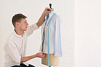 Tailor measuring blouse hanging on mannequin