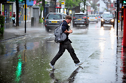 &copy; Licensed to London News Pictures. 6/06/2017<br /> A man jumping flooded road in Orpington,High Street,Kent.<br /> Heavy rain and some flooding this morning in Kent and the South East,UK. Shoppers and commuters get wet in Orpington High Street as the roads start to flood.<br /> Photo credit: Grant Falvey/LNP