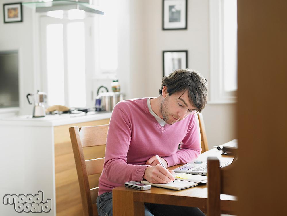Man sitting in kitchen writing in notebook