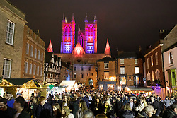 "© Licensed to London News Pictures. 08/12/2019. Lincoln, UK. The new Lincoln Cathedral floodlights could be seen at the annual Christmas Market for the first time this year. The market which attracts thousands of visitors every year was one of the first events to experience the new lighting which has been installed over the past year. The coloured lights change colours from red into blue during a moving sequence. Dr Anne Irving, programme manager of Lincoln Cathedral Connected, said that the commissioning of the new lighting system is a major milestone in the ongoing project.<br /> She said: ""We're delighted to be another step closer to the completion of the Old Deanery Visitor Centre next year.<br /> ""Lighting the cathedral is a very visual expression of the excitement we feel as the project nears completion.""<br /> She added that the new lights will not only be much more environmentally friendly, but also provide better illumination of the historic building. The Reverend Canon John Patrick, Subdean of Lincoln, said that lighting the cathedral sent out a powerful message of hope.<br /> He said: ""The imagery of light is a powerful metaphor in the Christian story; light overcoming darkness, good defeating evil and hope triumphing over despair.<br /> ""The lighting of the cathedral not only is a daily reminder of the beauty of the building but also an important image of God's presence in this city and county."". Photo credit: Dave Warren/LNP"